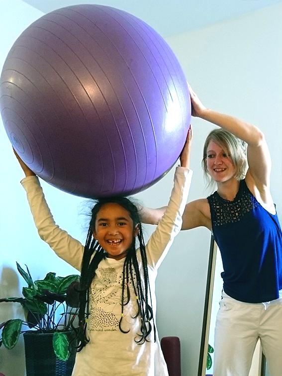 Kind und Frau, welche mit einem großen Ball spielen