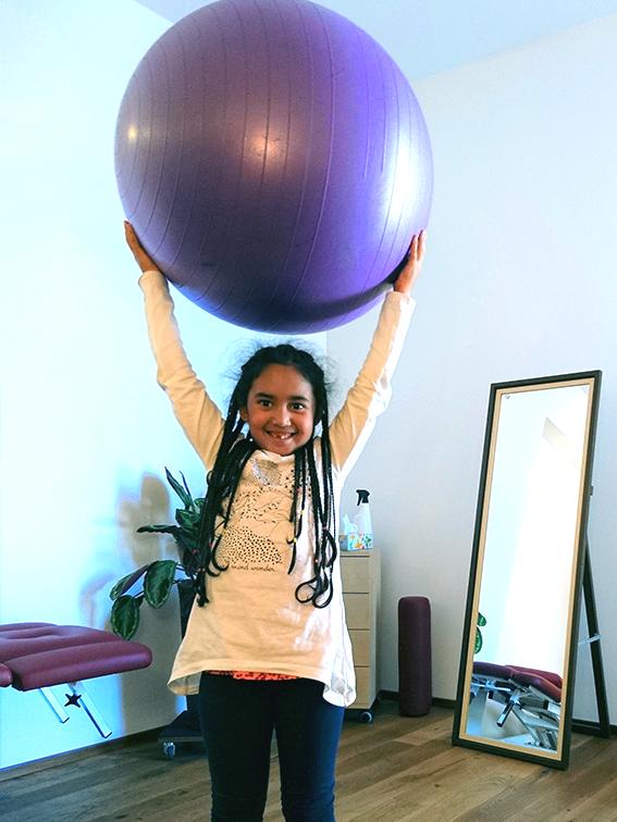 Ein Kind hält einen großen Ball über seinem Kopf