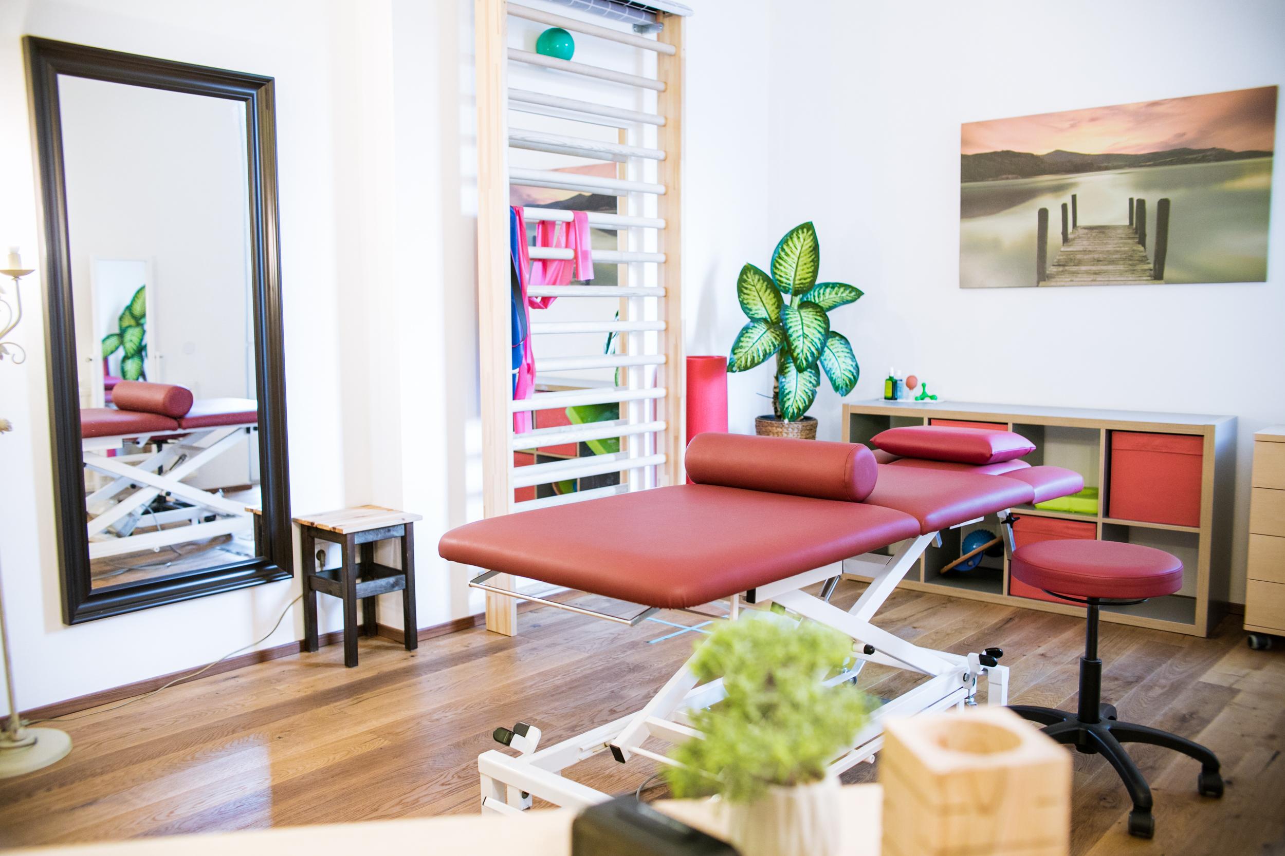 Roter Therapietisch in einem Behandlungszimmer