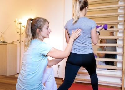 Astrid unterstütz eine Frau bei einer Übung mit Gewichten