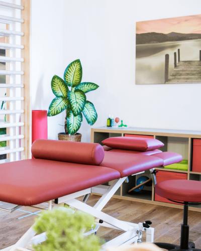 Ein roter Therapietisch mit einer Zimmerpflanze im Hintergrund